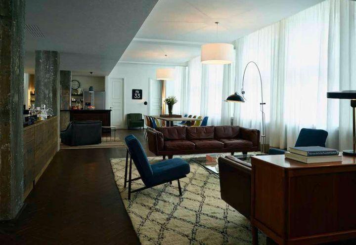 Uno dei loft esclusivi appena inaugurati a Berlino dalla Soho House. Openspace con salotto di ispirazione anni '60 in primo piano e tavolo da pranzo sullo sfondo