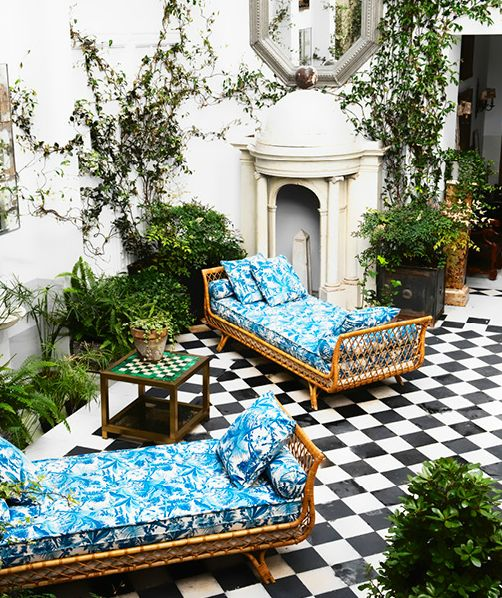 rattan chaise lounges, turquoise print, black & white tile floor.: