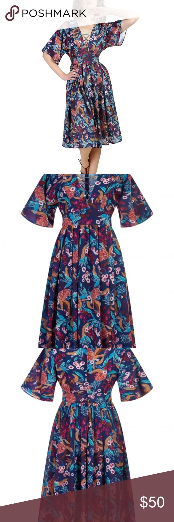 """Collectif Cathy Tropical Pineapple Dress Brand new with tags. Floaty kimono sleeves, panelled V neckline with lace up front, and a curved waistband. Her full skirt is gently gathered, and she fastens with a centre back zip. Cathy is made in our bespoke Tropical Pineapple fabric, a navy chiffon printed with vibrant blue leaves, red cherry blossoms, and quirky orange pineapples.  US size 6 / UK 10. 28"""" waist, 34"""" - 36"""" bust, 44"""" length Bright and Beautiful Dresses Midi"""