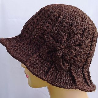 A top-down hat with a brim and a flower embellishment.