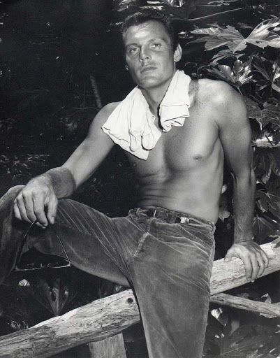 A young shirtless Adam West