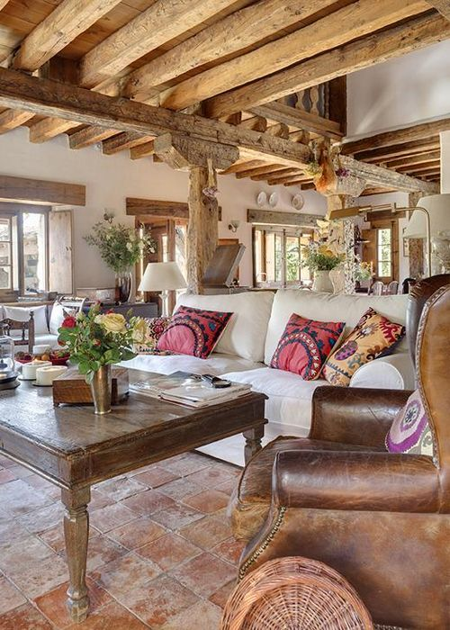Rustic beams, leather chair and colorful pillows.