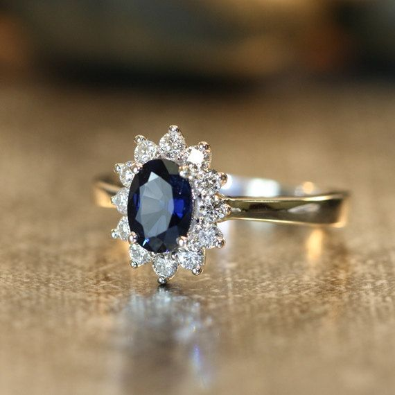 An 7x5mm oval shaped vibrant blue natural sapphire sparkles in the center of this 14k white gold halo ring setting with fastidiously sparkling