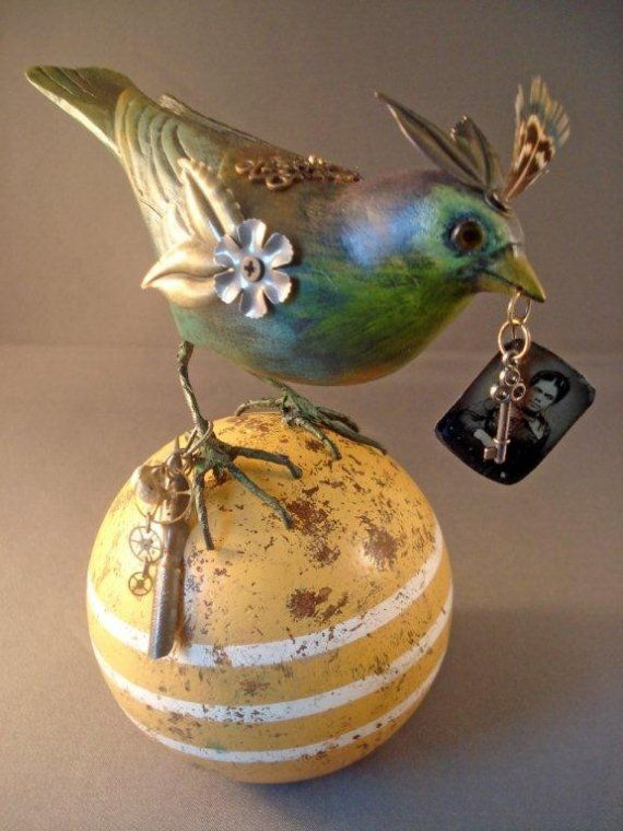 This one of a kind Steampunk Bird is mounted to a vintage wooded croquet ball. I have taken an old hand carved wood bird with glass eyes and completely re-painted and finished him. I have adorned the bird with little metal doo-dads including a lovely Vintaj filigree piece and a tiny real bird feather on the top of its head. I have mounted him to the wood croquet ball and added some neat vintage elements around his leg including some old buttons and a tip to a vintage fountain pen. In his…