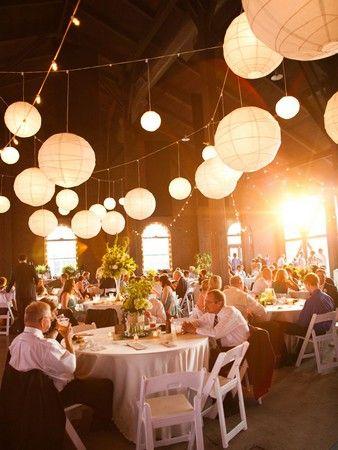 Décoration de réception avec des lanternes suspendus blanches dans un endroit rustique