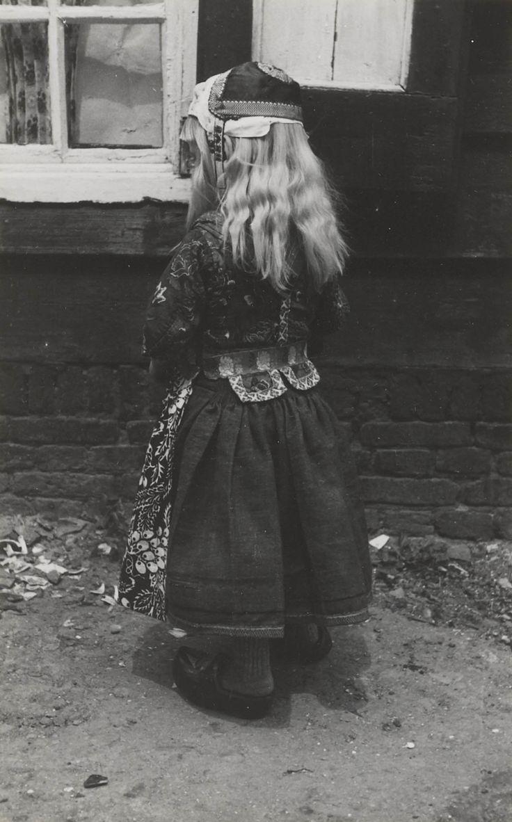 Jongen in Marker streekdracht. Hij is onder de vijf jaar en gekleed in rokkendracht. Hij is als jongen ondermeer herkenbaar aan de twee pandjes aan de achterzijde van zijn jak, het model van zijn muts en zijn gebloemde schort. De jongen is gekleed in pinksterkleding, het zogenaamde 'Pinkster-bas'. 1943 #NoordHolland #Marken