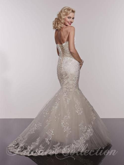 Strapless Sweetheart Neck. Slim trumpet flare Skirt. Lace gown with plain tulle underlay. Lace hemline. Lace-up back. Chapel train. Available Exclusively at Spring Lake Bridal & Tuxedos (BACK)