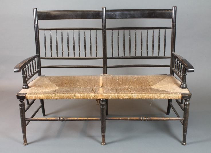 """In the manner of William Morris, an ebonised """"Sussex"""" style double chair back settee with turned spindles, scroll arms and rush seats, raised on ring turned tapered legs, late 19th Century 47""""w"""