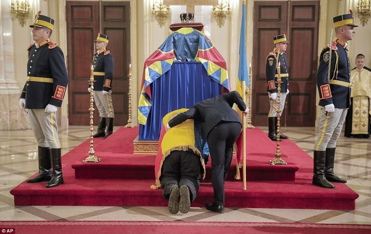 A steward checks on a man who kneeled by the coffin of late Romanian King Michael, at the ...