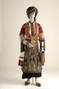 Γυναικεία φορεσιά Καραγκούνας-Θεσσαλία Description: Είναι η νυφική και γιορτινή φορεσιά των χωρικών του θεσσαλικού κάμπου. Χαρακτηριστικά στοιχεία της είναι το βαρύ, λινό πουκάμισο με το αυστηρό, μαύρο κέντημα και τα μακριά κρόσσια καθώς και τα δύο πολύπτυχα βαμβακερά φουστάνια. Τη φορεσιά συμπληρώνουν η τσόχινη ποδιά και τα καβαδομάνικα κεντημένα με πολύχρωμα ή χρυσά κορδονέτα. Στο κεφάλι, στο στήθος, στη μέση και στην ποδιά φορούν πολλά κοσμήματα, κυρίως αλυσίδες με νομίσματα. Ο…