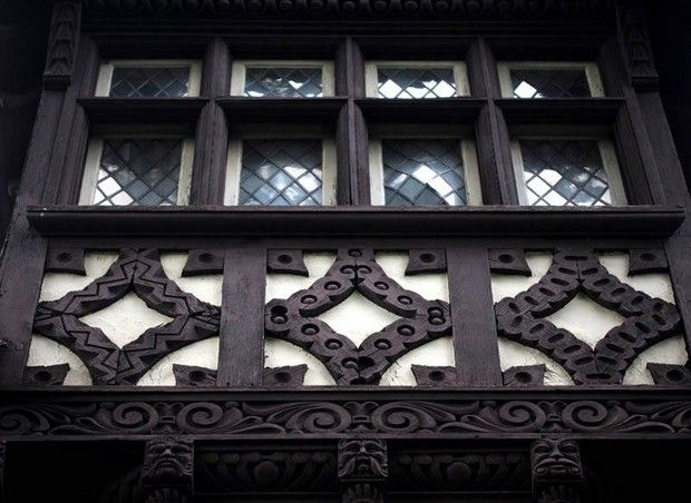 Ornate carved details on the bottom of a window of a Tudor