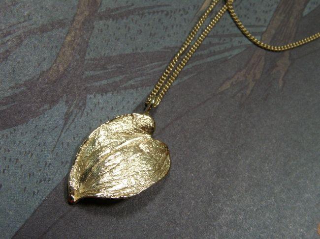 * necklaces   oogst-sieraden * Collier met hanger * Geelgouden blad hangend aan lang verfijnd gourmet collier *