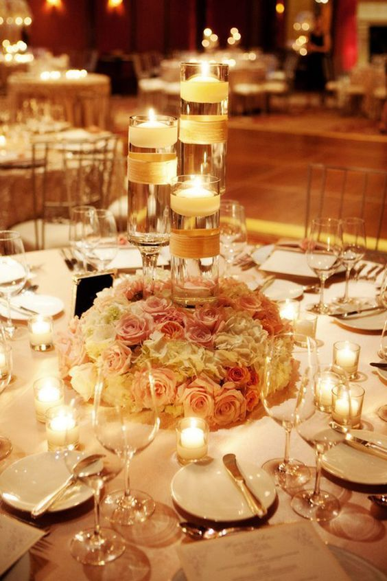 images of low floral centerpieces with hurricane candles | Centerpiece: Three-tiered hurricane candles with flower wreath:
