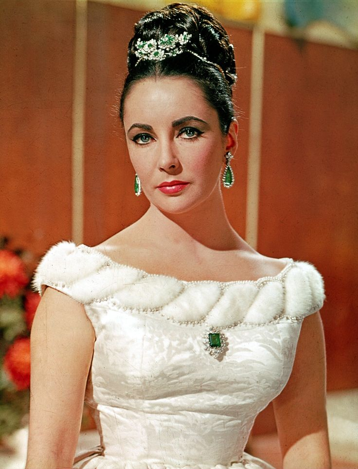Elizabeth Taylor in a publicity photograph wearing her Bulgari platinum, emerald and diamond en tremblant brooch in her hair,a Colombian emerald brooch and Colombian emerald and diamond earrings in 1963. Discover the history of Bvlgari and the famous fashion women who wear it: http://www.thejewelleryeditor.com/jewellery/bulgari-history-of-style-celebrities-iconic-design/ #jewelry