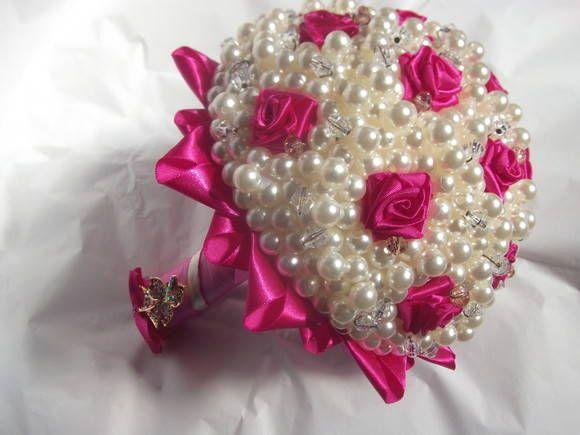 Buquê de pérolas e cristais, feito com mini rosas de cetim fúcsia. Detalhe e acabamento em strass e voil pink. Broche em tons cor de rosa no cabo (opcional). Solicitamos que a encomenda seja feita com antecedência mínima de 20 dias.