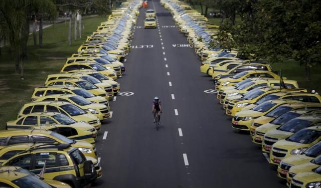 A man rides his bicycle between taxis parked on the street during a protest against the online car-sharing service Uber in Rio de Janeiro, Brazil July 24, 2015.