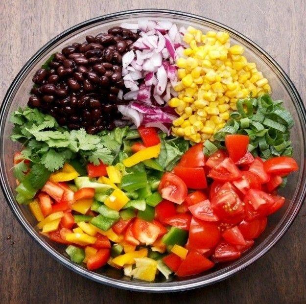 Você coloca alface, coentro, feijão, cebola, milho e tomate bem bonitinhos numa tigela, mistura e joga um molho esperto de abacate por cima. Veja aqui a receita.