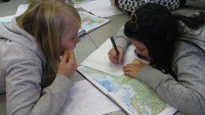 Kaksi tyttöä tekee luokan lattialla tehtäviä kartan kanssa.