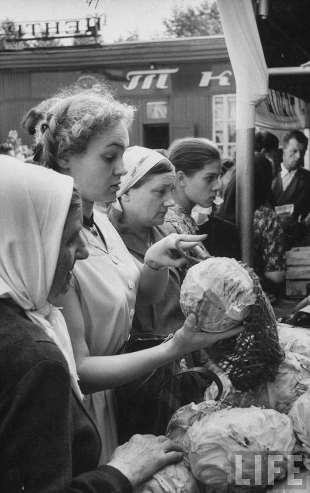 Buying vegetables in a market, by Lisa Larsen.