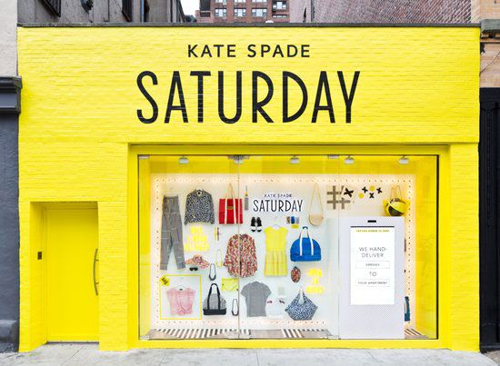 Bright yellow shop front with Kate Spade Saturday clothes pinned neatly to the wall