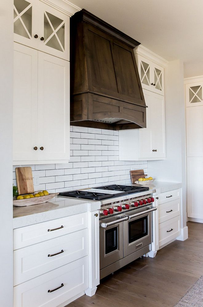 """The custom Alder wood hood is stained in a """"dark walnut"""" color. Cabinets are SW Alabaster.Timber Frame Home with Farmhouse-Inspired Interiors"""