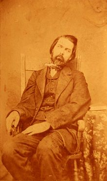 A post-mortem photograph of a middle-aged man. The body is arranged so as to appear lifelike (circa 1860).