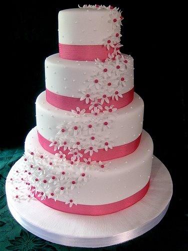 tortas de 4 pisos en color blanco con chispitas en rosado y cintas rosadas.