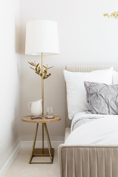 Chic bedroom features a light taupe velvet bed, West Elm Roar + Rabbit Pleated Bed, dressed in gray pin-tuck bedding, Organic Cotton Pintuck Duvet Cover + Shams, placed next a wood and brass nightstand with built-in lamp. #LuxuryBeddingApartmentTherapy