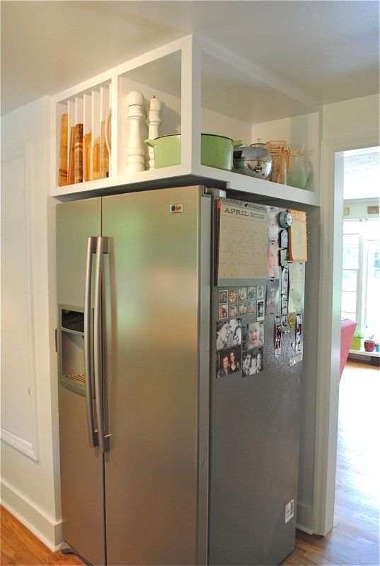 Here, an awkward corner refrigerator becomes super handy with built-in overhead shelving. An open area holds large items like a slow cooker, while  slotted sections keep cookie sheets and cutting boards in place.