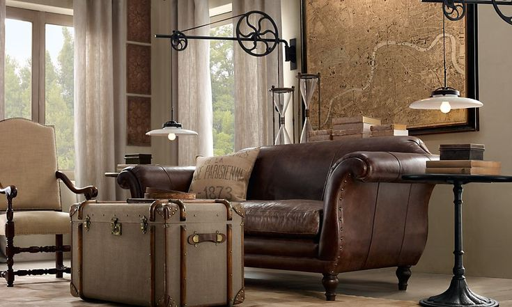 Ooh, a blend of the more 'feminine' sofa w/the leather. The trunks and iron tables rock as does the chair...just replace the old London map w/one of New Orleans...