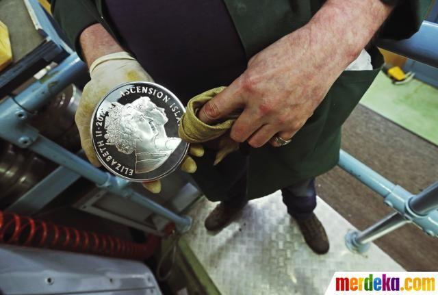 "Seorang pekerja tengah memoles koin mahkota "" 60 Crowns"" di tempat pencetakkan uang di kepulauan Pobjoy Mint, Inggris."