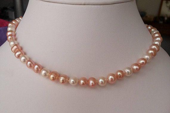 Ce collier ras de cou est composé de perles de culture deau douce arrondies, couleur pêche et blanche. Le fermoir est en argent plaqué or. - longueur: 41 cm - diamètre des perles pêche: environ 0.75 cm - diamètre des perles blanches: environ 0.7 cm - les perles sont arrondies, mais pas tout-à-fait rondes - fermoir en argent plaqué or  Ce collier est très élégant et ses couleurs douces le rendent facile à porter.