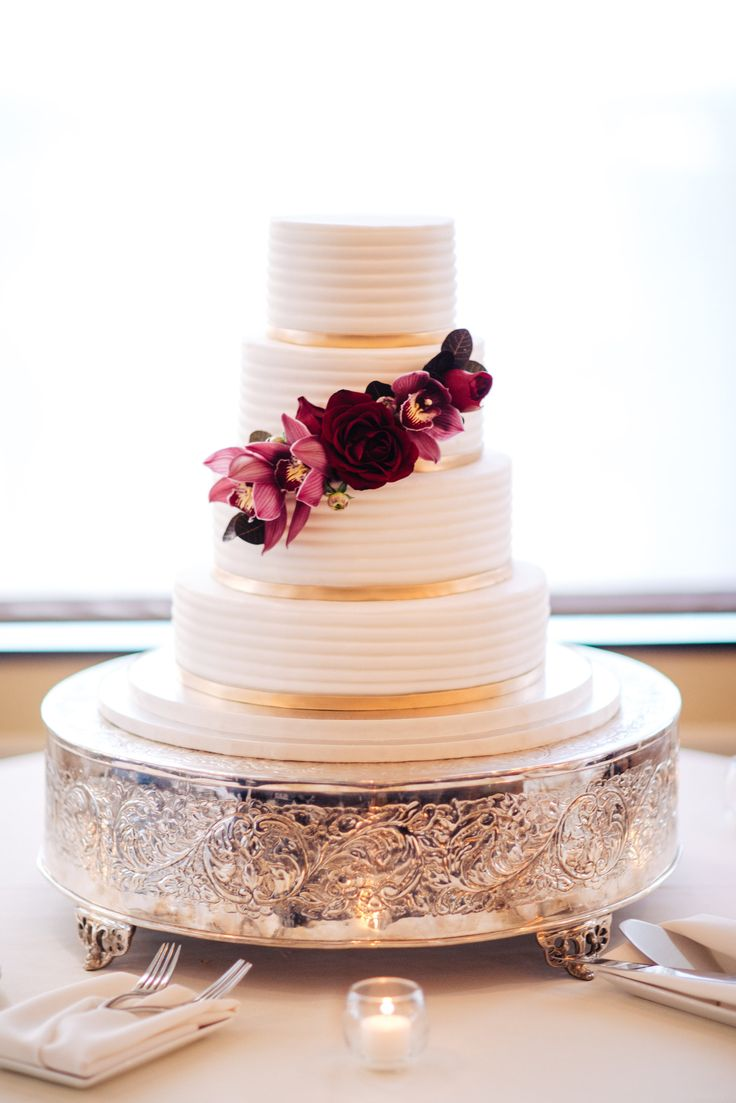 a classic yet modern wedding cake is adorned with black magic rose and chocolate cymbidium orchids.