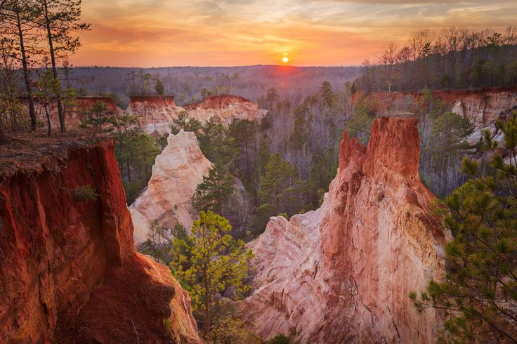 Sunset in South Georgia at Providence Canyon. The canyon formation, made up of a kaleidoscope of coloured sands and clays, owes its existence to destructive early farming practices in the 19th century as is was unknown at the time that the undulating hills were made up of deep sand deposits below a very thin crust of clayey topsoil. Once the topsoil had been disturbed the natural elements did the rest with the canyon progressively deepening over the subsequent 150 years. The dramatic…