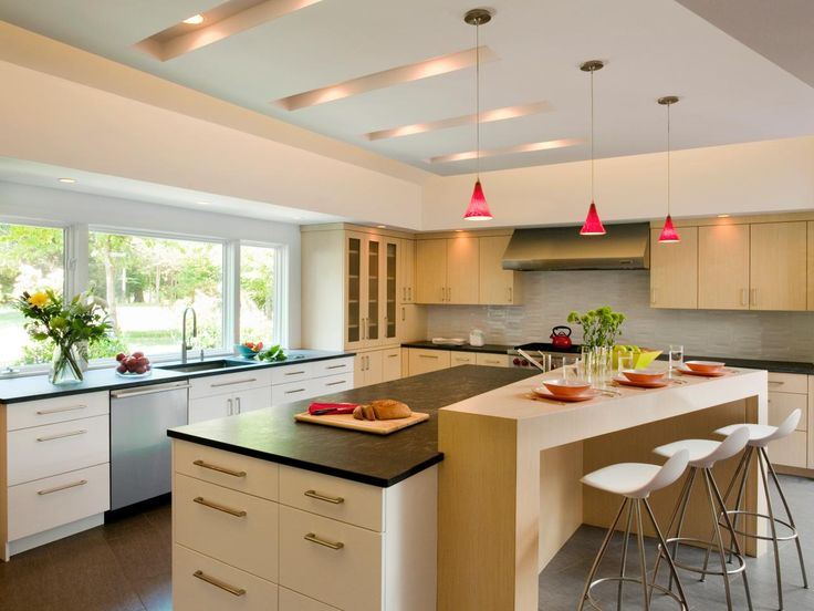 This open, contemporary kitchen has high white ceilings and light wooden cabinets. The large island features a dark countertop and wooden bar dining area. Red pendant lighting adds a touch of color to the light kitchen.