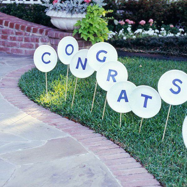 Wooden Sign Graduation Party. Direct your guests with this wooden sign to your front walk. Cut letters from blue paper and glue to paper plates. Attach wonder dowels and stick into the lawn for simple graduation party decor without costing too much. http://hative.com/graduation-party-ideas/