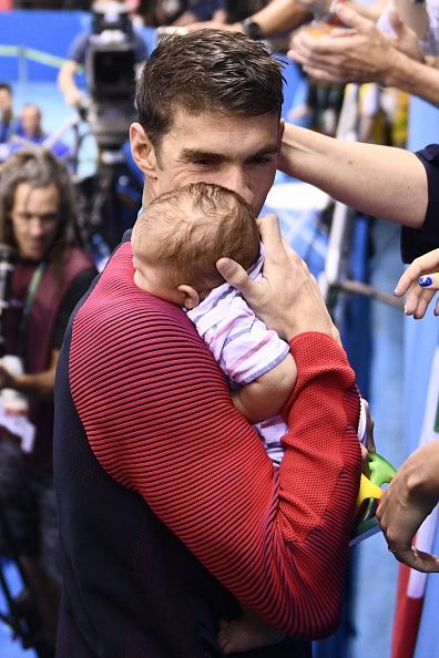 USA's Michael Phelps holds his son Boomer after he won the Men's 200m Butterfly Final during the swimming event at the Rio 2016 Olympic Games at the...