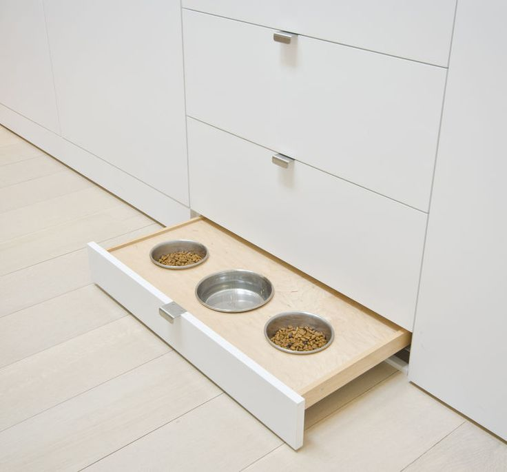 Interior design ideas: smart pull-out pet food bowls integrated into a white kitchen cabinet