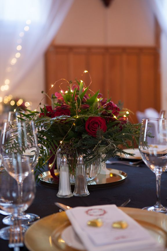 The Chapel - black linen, gold charger plates, red florals with seed lights, Marquee canopy with fairylights by A Touch of Elegance - Beautiful head table of greenery, gold candlesticks, seed lights - florals and head table by Kerin Greville. With thanks to Rei Bennett Photography.