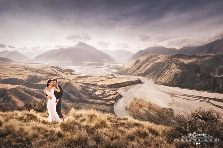 Cute couple snuggle atop amazing and stunning New Zealand scenery.  More wedding photography by Anthony Turnham at www.snapweddingphotography.co.nz