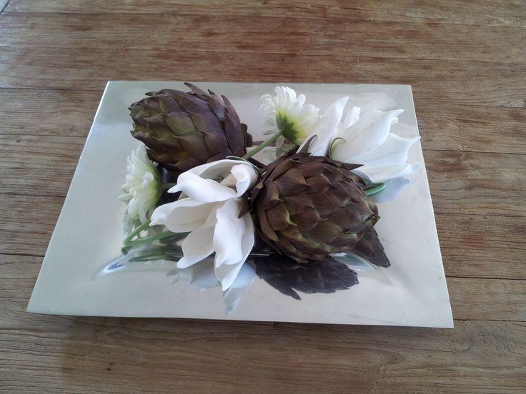 Met enkele mooie kunstbloemen kan je eenvoudig een mooi bloemstuk op tafel maken.
