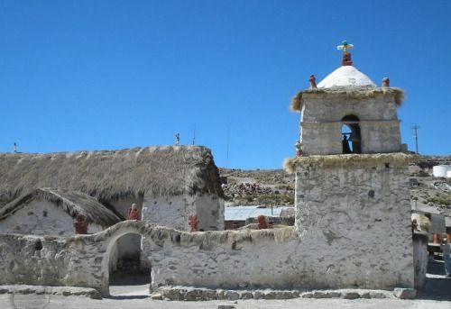 Iglesia de Parinacota La Iglesia de Parinacota fue levantada en 1670, de barro y piedra, y está emplazada en el centro de la localidad. Construida en adobe y tiene 33 metros de largo y 6 de altura. En la iglesia se erige, a modo de campanil, una torre cuadrada y de dos niveles,. se pueden ver muros con murales del 1700, simbolizando los instantes más trascendentales de la Pasión de Cristo, actos sacramentales.. La arquitectura se asemeja con el estilo mestizo del altiplano, que es…