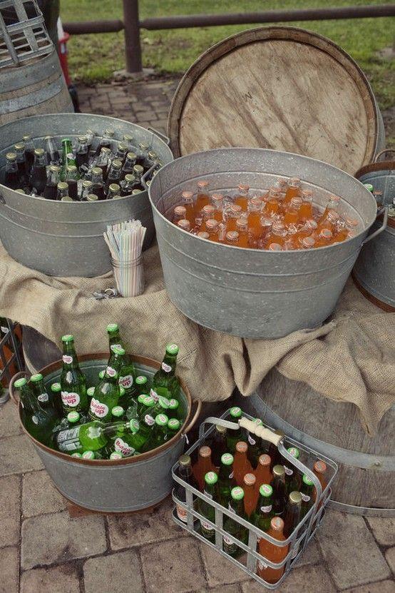 Galvanized buckets of drinks on make shift barrel tables.