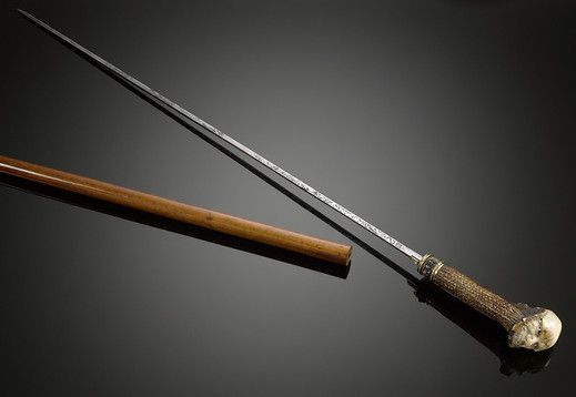 The ultimate tool in discreet self-defense, this fascinating French walking stick reveals a deadly blade with a pull of the handle. The beautifully engraved blade is attached to an antler handle, which has been delicately carved to depict the expressive faces of two men. Weapons canes such as this reflect the more sinister side of the systems cane, and are
