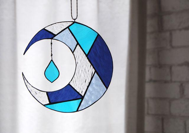 ステンドグラスの技法で作成しました。月の雫が揺れるオーナメントサンキャッチャーです。色々なテクスチャー、のガラスを使用しています。自然光の下でキラキラした光が揺れてとてもキレイです。月は満ち欠けを繰り返すため、成長の象徴とも言われているそうです。ハンダは...