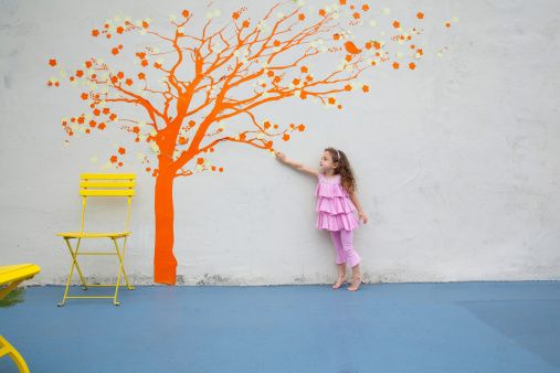 Stock Photo : Girl pointing to orange tree mural on wall