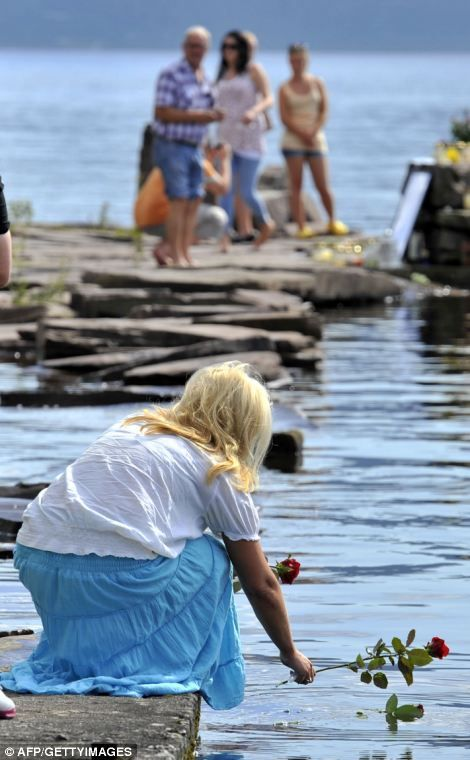 Atrocity: Anders Breivik, seen left in court, fired indiscriminately on students at the summer camp on Utoya, where shell-shocked mourners lay flowers on the surface of the lake in the days after the mass shootings, right