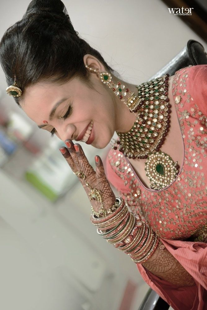 Blushing bride in a pink lehenga and heavy poli jewellery and long chandbalis.  Photography courtesy of Water Photography.  Find more Indian Wedding inspirations at www.jivaana.com #candidphotograhy #inspiration #shopping #weddings