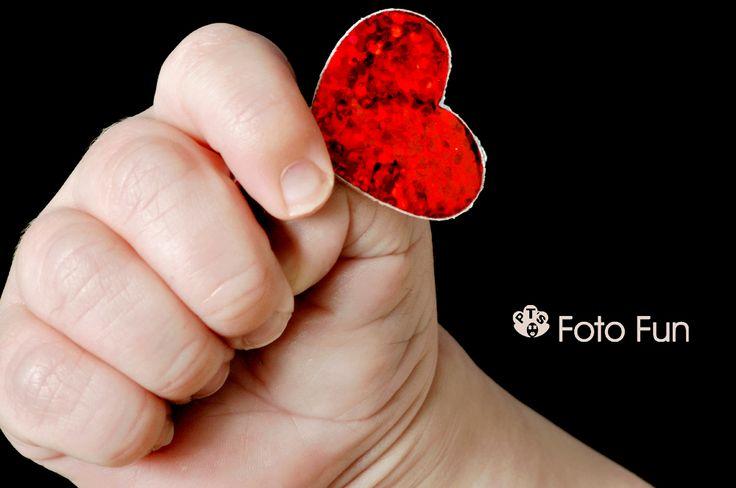 Baby hand holding heart