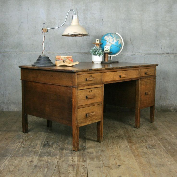 A large vintage oak desk produced in the 1940s/50s, primarily for use as school teacher desk. Constructed from solid oak and oak veneers, the desk features three solid oak drawers to the left side, a large central drawer and two drawers to the right. In great vintage condition, the oak has a striking patina. Some of the drawers handles are quite worn but this all adds to the character of the desk. Please take a look at the photographs for more detail. Dimensions: Height: 76cm Width: 152cm…